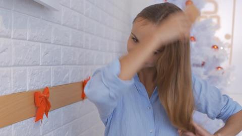 Blond Girl Brushes Long Hair near Christmas Tree Footage