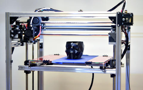 3D printer printing a model in the form of black skull close-up Photo