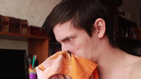 young guy has a runny nose, wipes his nose with a handkerchief, sneezes into his Live Action