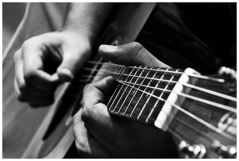 Close up of male hands playing guitar フォト
