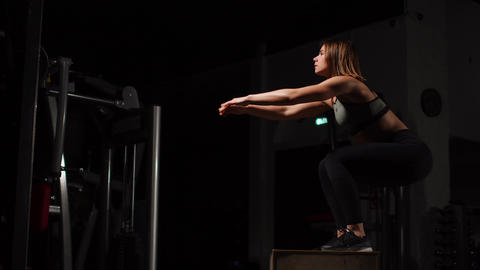 Beautiful female fitness athlete performs box jumps in a dark gym wearing black Footage