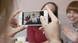 Young beautiful caucasian girl is making a photo on the smartphone of her two Footage