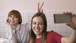 Two young Caucasian beautiful girls sit in a cafe and do selfie, laugh, smile Footage