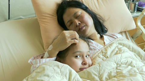 Tween girl in hospital bed with ill mother Image