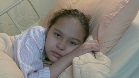 Asian American tween girl in hospital bed dolly in Footage