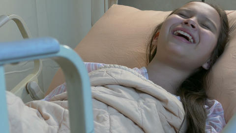 Asian American tween girl in hospital bed laughing happily Footage