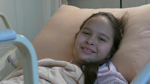 Asian American tween girl in hospital bed smiling Footage