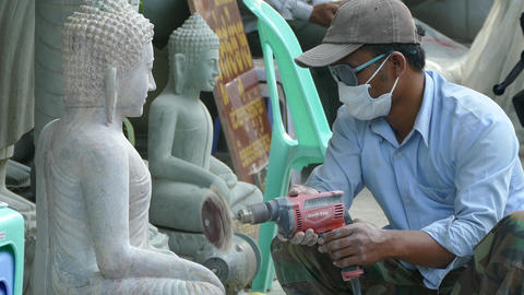 Polishing a Buddha statue in the streets of Phnom Penh Footage