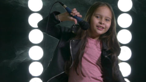 Young girl singing with microphone on stage Footage