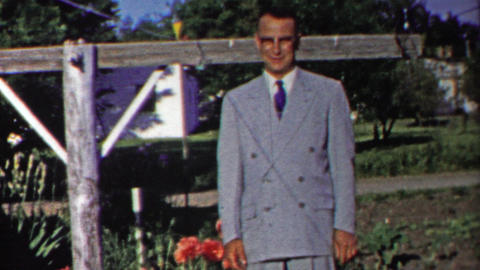 1958: Dapper man in gray double breasted suit posing by flowers Footage