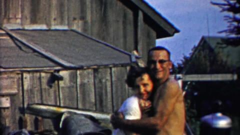 1958: Lovers embrace at farm hug kiss man carries woman off Footage