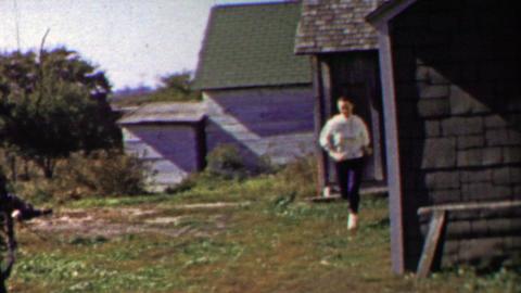1958: Woman closes door runs rural summer sunny farmhouse Footage