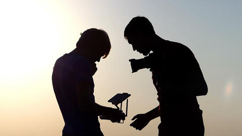 Two men look at a drone control panel in slo-mo Image