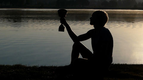 Sportive man sits on a lake bank looking at a winner bowl in slo-mo Live Action
