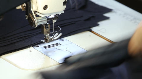 Tailor sews clothing on the sewing machine Live Action