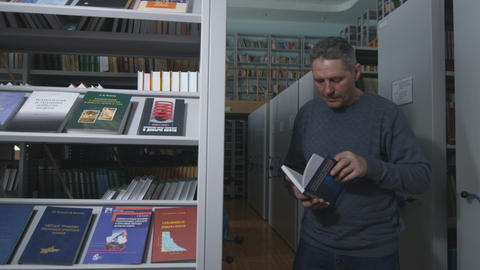 Man Walks from behind Book Shelf in Plant Library Footage