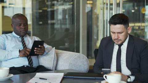 Two business colleagues in formal wear sitting and using their smartphone and Footage