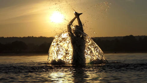 Blond man raises the lake water to entertain at sunset in slo-mo Footage