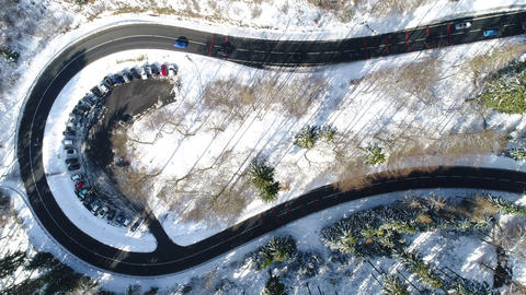 Aerial view of a curve through wintery forest Live Action