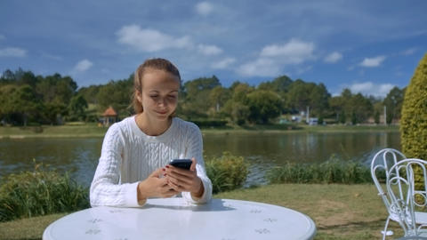 Blonde Girl Sends Sms at Table in Cafe by River Live Action