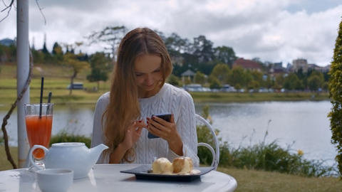 Girl Surfs Internet Sitting at Table with Dishes Footage