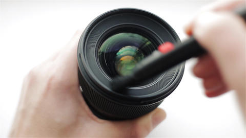 Hands of photographer or videographer cleans front glass of a lens from dust and Footage
