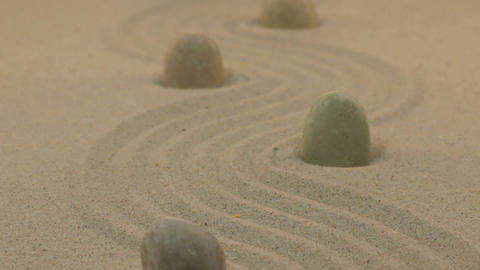 Approximation of white stones standing on zigzag lines from sand. Dolly Footage
