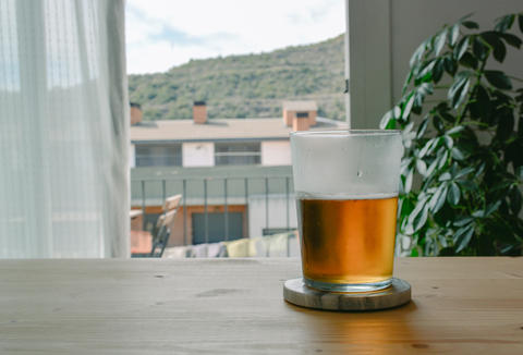 Glass of Beer on a Wooden Table Photo