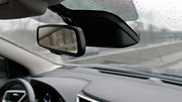 View of car back mirror while driving through the rain Footage