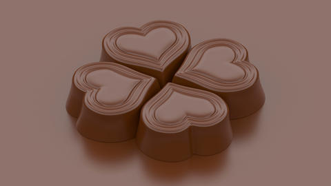 Four rotating heart shaped bonbon sweets made of milk chocolate on brown Animation