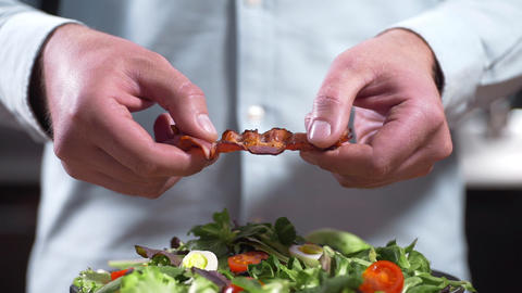 The cook breaks a crisp piece of bacon, chef cooks salad with pieces of fried Live Action