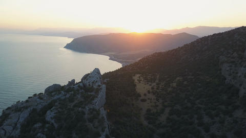 Flight over rocks and beautiful bay surrounded by mountains at sunset in Crimea Footage
