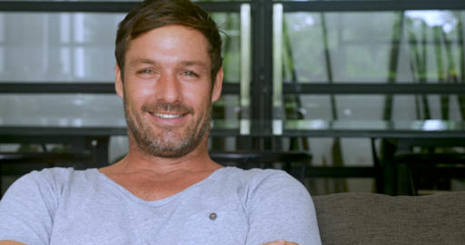 Handsome man in his 30s or 40s sitting on sofa with a scruffy beard smiling and Footage