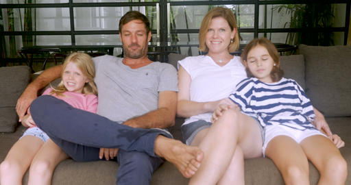 Happy family sitting on a sofa together smiling and giving a thumbs up in their Footage
