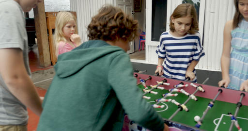 Young girls playing foosball against young boys at a party or summer camp Footage