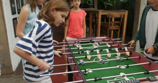 Two young girls scoring a goal against two boys playing foosball and celebrating Live Action