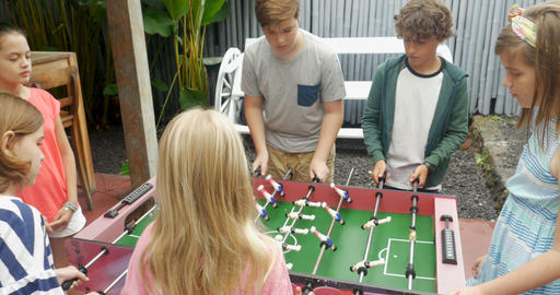 Young girls against young boys playing foosball and the girls score to win the Footage