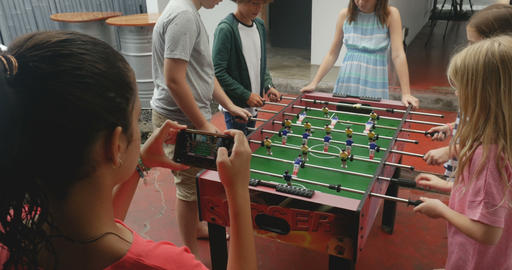 Young cute girl taking photos of her friends playing foosball with her mobile Footage