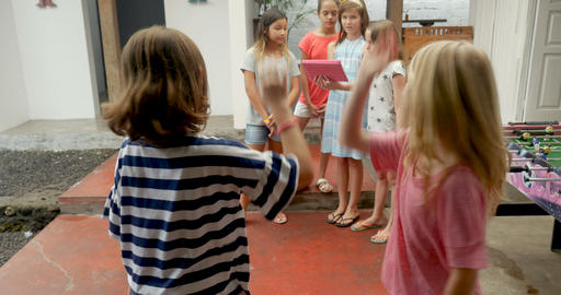 Two young girls high five and join their diverse group of mixed racial friends Footage