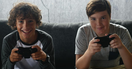 Two friends or brothers smiling and having fun playing a video game with Footage