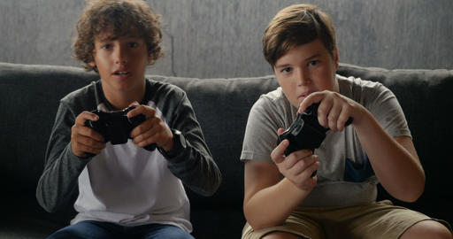 Two boys playing video games steering their gaming controllers and having fun Footage
