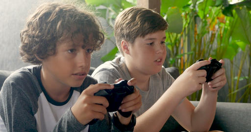 Two boys age 11 - 13 playing video games with hand held controllers talking and Archivo