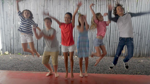Happy diverse multi ethnic group of boys and girls age 11 - 13 jumping up Live Action