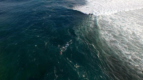 Aerial view of a surfer paddling out to the lineup through the channel Footage