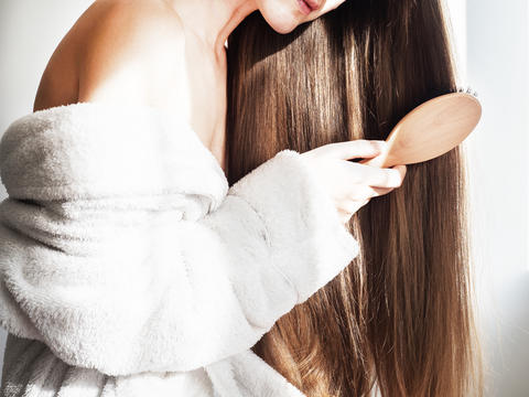 Cute, young woman combing her hair フォト