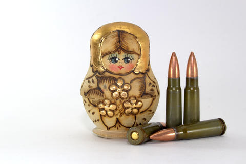 Russian matryoshka and several cartridges for a Kalashnikov assault rifle フォト