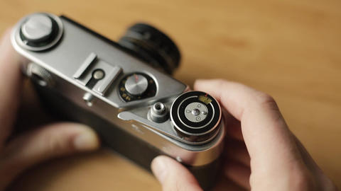 An old vintage film camera in the hands of a young beginner photographer. He Footage