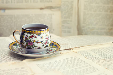 An old cup of coffee on the background of old sheets from the book Photo