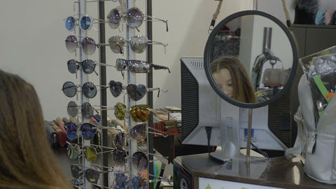 Pretty young teenager girl trying various brands of sunglasses in a shop Footage