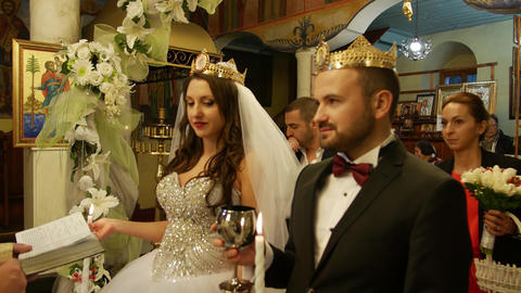 Newlyweds drinking wine during marriange ritual in a church Live Action